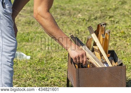 Close Up, A Man Hand Lights Firewood With A Match In A Barbecue On The Street
