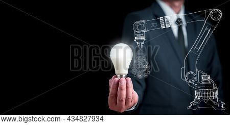 Businessman Holding A White Light Bulb Shines Brightly. The Arm Of An Industrial Robot Holds A Cog T