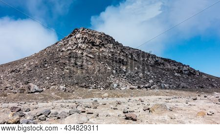 A Rock Devoid Of Vegetation, Against A Background Of Blue Sky And Clouds. Volcanic  Stones Are Scatt