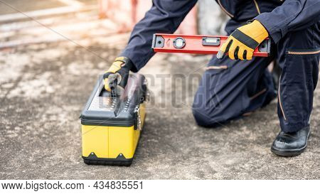 Asian Maintenance Worker Man Holding Red Aluminium Spirit Level Tool Or Bubble Levels And Working To