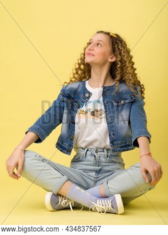 Carefree Teen Girl Sitting On Floor In Lotus Pose. Portrait Of Beautiful Girl Wearing Stylish Denim