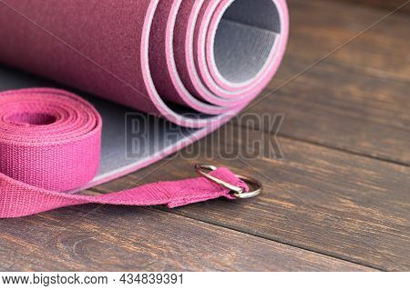 Yoga Mat, With Yoga Strap On Wooden Background. Essential Accessories For Practice Yoga And Meditati