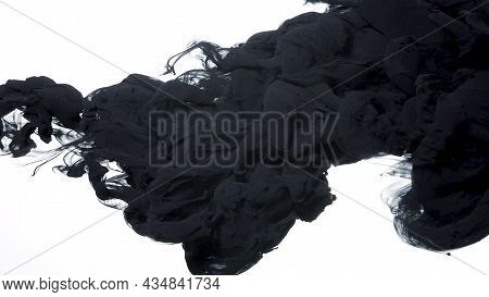 Black Watercolor Ink In Water On A White Background. Black Cloud Of Ink On A White Background. Abstr