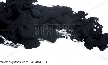 Black Cloud Of Ink On A White Background. Abstract Background. Drops Of Black Ink In Water. Colored
