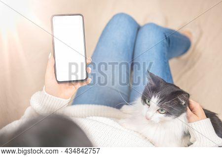 Woman Using Smartphone Blank Screen Frameless Modern Design While Lying On The Sofa In Home Interior