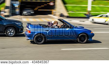 Geo Metro Convertible Old Car Driving On The Street. Blue Suzuki Swift Convertible In Motion. Moscow