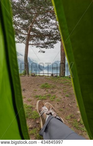 Man Relaxes In Tent After Hike And Looks On Lake And Camp Bench Between Pine Trees. Exploring North