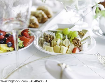 Table Served For Banquet. Plates With Fruits And Appetizers, Transparent Modern Stylish Wine Glasses