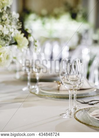 Table Serves For Banquet. Transparent Wine Glasses, Plates With Napkins And Shiny Cutlery On White T