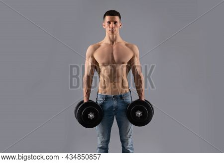Weight Training. Sportsman Hold Dumbbells Grey Background. Strength Training Workout