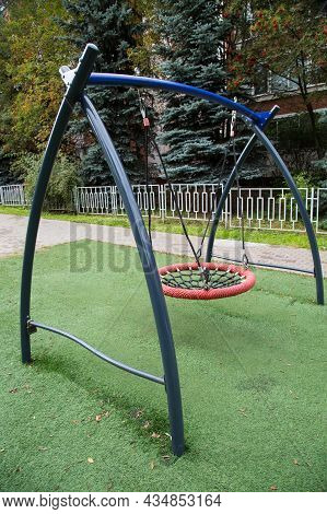 A Metal Swing In The Form Of A Ring With Intertwined Synthetic Ropes In The Center Against A Backgro