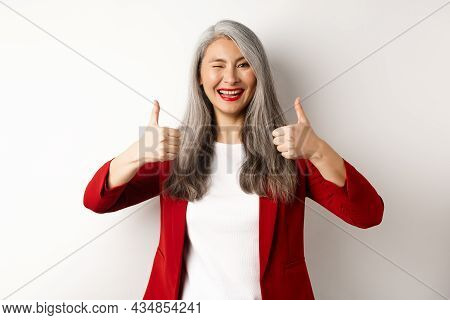Cheerful Asian Mature Woman Winking, Smiling Pleased And Showing Thumbs-up In Approval, Like And Agr