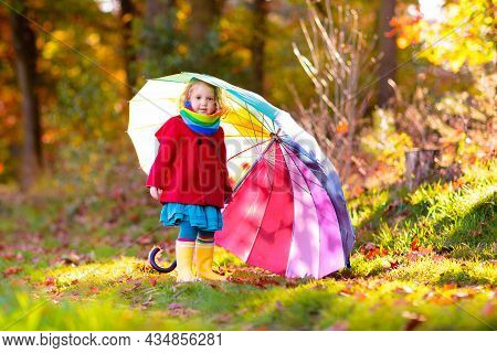Kid Playing Out In The Rain. Children With Umbrella And Rain Boots Play Outdoors In Heavy Autumn Rai