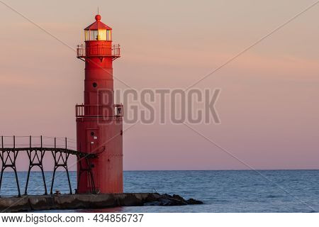 A Red Breakwater Lighthouse Along Lake Michigan In The Last Moments Of A Setting Sun.
