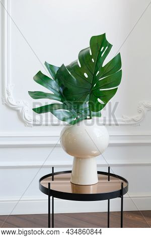 White Ceramic Vase With Monstera Leaves On A Mirrored Coffee Table Against A White Wall With Stucco