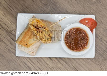 Overhead View Of Loaded Breakfast Burrito With Meat And Eggs Cut In Half For Easier Handling Served