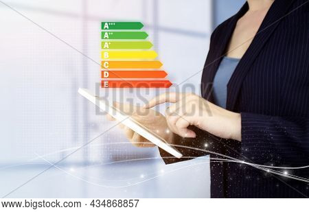 Energy Efficiency Concept. Hand Touch White Tablet With Digital Hologram Energy Efficiency Sign On L