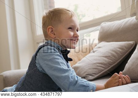 Little Blonde Boy Folded His Hands For Prayer And Smiled As He Turned To God. A Boy Prays By The Cou