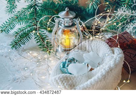 Christmas Toys In A Knitted Hat Lie Under The Christmas Tree Next To A Decorative Stylized Lamp. A C