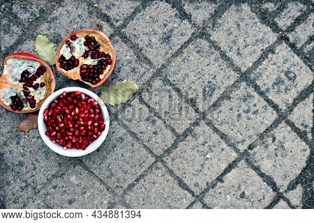 Peeled Red Pomegranate Seeds And Ripe Pomegranate Halves On A Stony Gray Background.