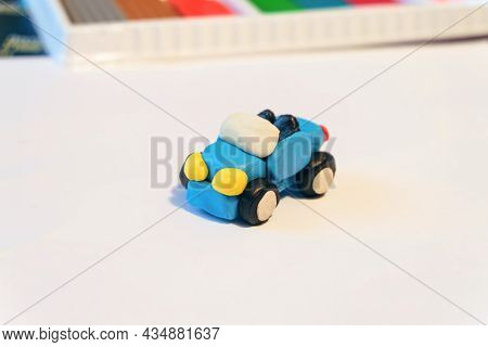 Small Coupe Car Made Of Colored Plasticine. Hand-made Children's Toy On A White Surface.