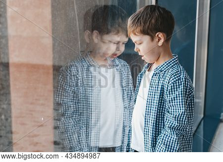 Boy In Shirt Looks Out The Window. Reflection Of A Boy In The Window. Light And Dark Side Of The Chi
