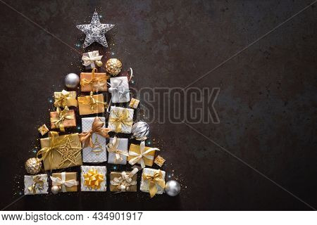 Holidays background with Christmas gift boxes and laid out in the shape of a Christmas tree, top view