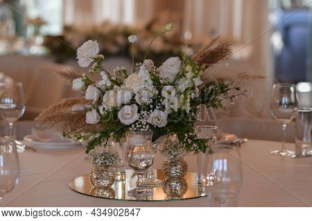 White Tablecloths With Clear Vases And White Flowers And Fern Arrangements. Golden Colored Plates, P