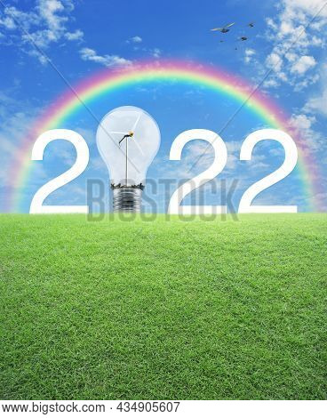 2022 White Text And Light Bulb With Wind Turbine Inside On Green Grass Field Over Rainbow, Birds And