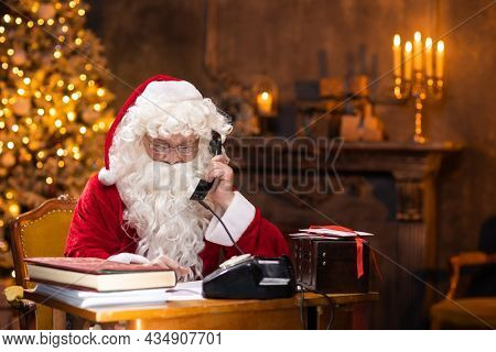 Workplace of Santa Claus. Cheerful Santa is working using vintage phone while sitting at the table. Fireplace and Christmas Tree in the background. Christmas concept.
