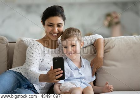 Happy Mixed Race Family Using Funny Mobile Applications.