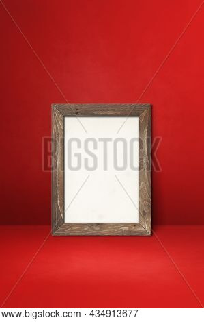 Wooden Picture Frame Leaning On A Red Wall. Blank Mockup Template