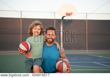 Father And Son Playing Basketball. Portrait Of Dad Embracing Little Boy Who Holding Basketball Ball
