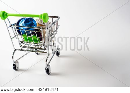 Trolley With Used Aluminum Coffee Capsules Isolated On A White Background. A Concept For Processing