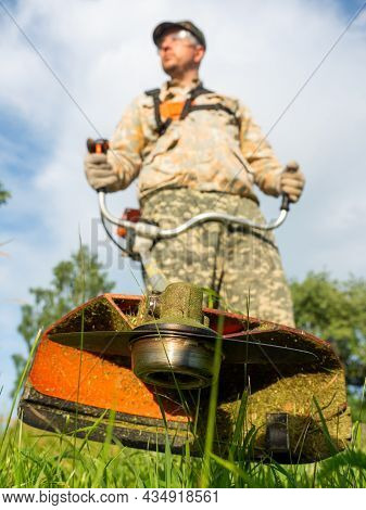 A Male Worker Mows The Grass With A Gasoline Trimmer. Bottom View, Selective Focus On The Trimmer Bl