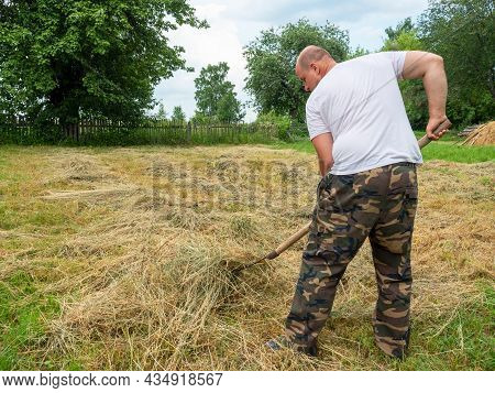 A Middle-aged Man, Dressed In Trousers And A T-shirt, Collects Grass In A Haystack With A Fork. The