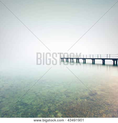 Pier Or Jetty Silhouette In A Foggy Lake. Garda Lake, Italy