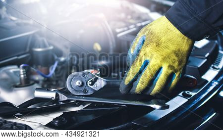 Car Mechanic Picking Up Socket Wrench And Tools On The Car Body In The Repair Garage