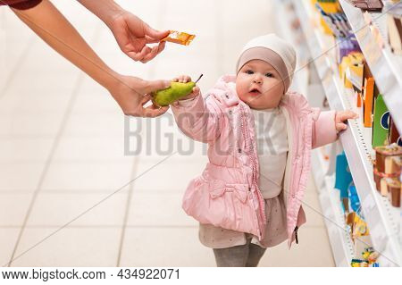 Shopping. Portrait Of Cute Child Is Standing Near The Shelf With Products, And Will Choose Between A