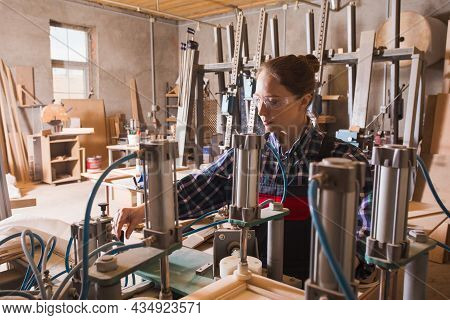 Experienced Female Craftman Work With Woodworking Machinery. Furniture Production
