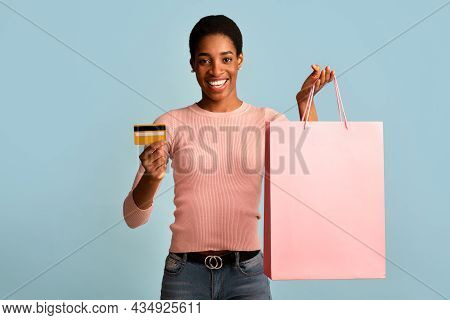 Shopping Concept. Happy Black Woman Holding Credit Card And Pink Shopper Bag