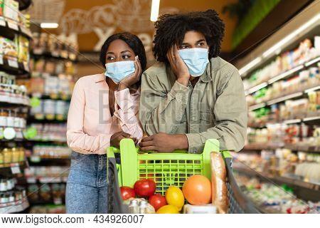 Unhappy Black Couple Shopping In Supermarket Struggling During Financial Crisis