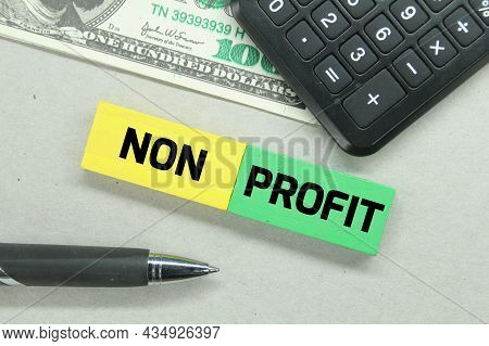 Calculators, Pens, Banknotes And Colored Boards With The Word Non Profit
