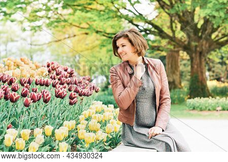 Outdoor Portrait Of Happy Young Woman Enjoying Nice Day In Spring Park With Tulip Flowers