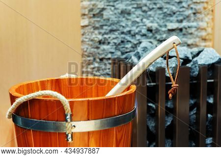 A Fragment Of A Wooden Bucket In The Bath. Equipment For A Sauna On A Background Of A Fireplace With