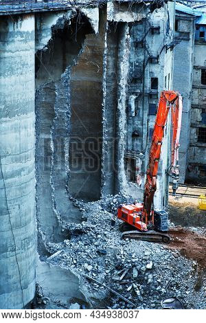 Dismantling A Dilapidated Building Using Heavy Equipment. Reinforced Concrete Cutting With Hydraulic