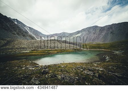 Scenic Alpine Landscape With Turquoise Glacial Lake Among Mountains Under Cloudy Sky. Atmospheric Sc