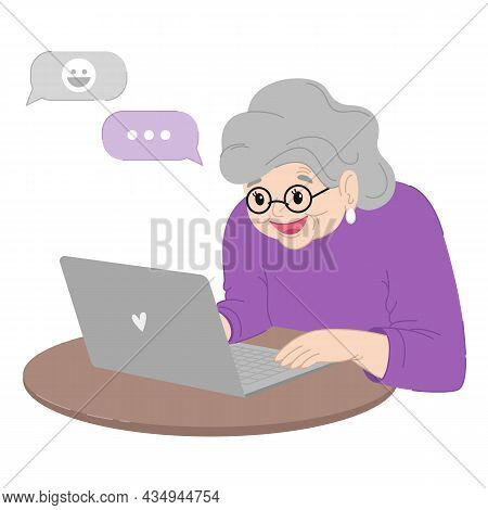 Cute Happy Grandmother Is Sitting At The Laptop.