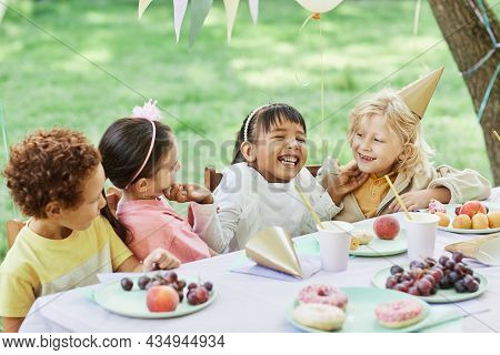 Portrait Of Smiling Little Girl With Friends At Picnic Table Outdoors Enjoying Birthday Party In Sum