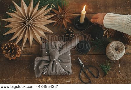 Christmas Advent. Hand Holding Candle And Stylish Christmas Gift Wrapped In Fabric, Scissors, Paper